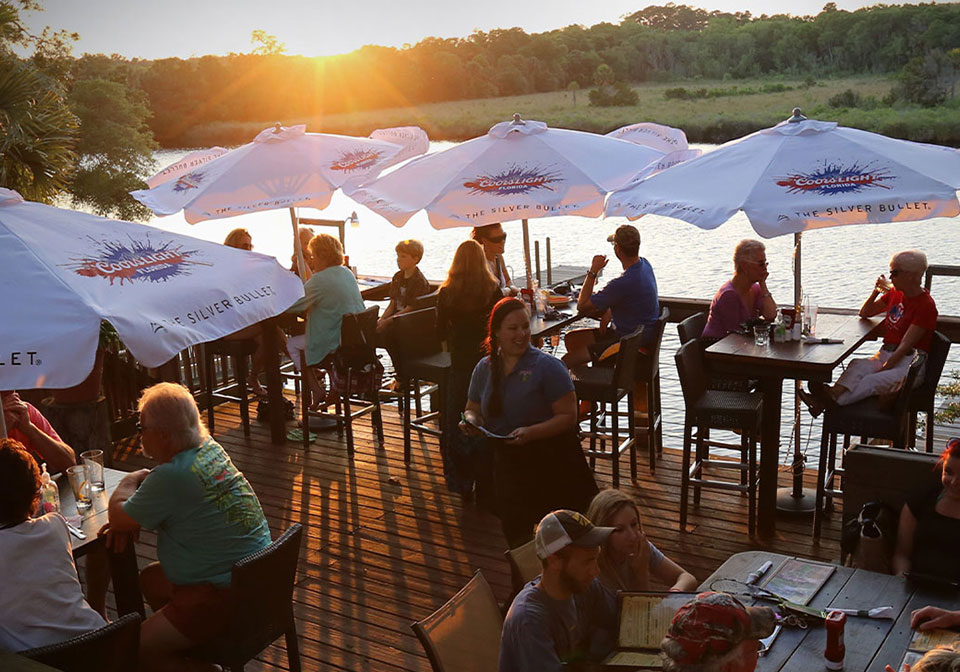 A packed RiverGrille outdoors seating area during the sunset.