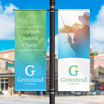 Two street lamp banners with the new City of Groveland logo.